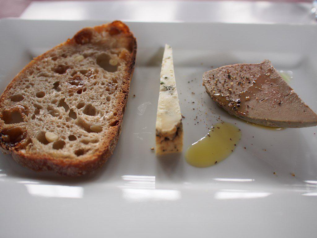 試作品の石窯で焼いたレーズンと松の実のパン、同じく試作品の羊乳ブルーチーズ、羊レバーのコンフィ。